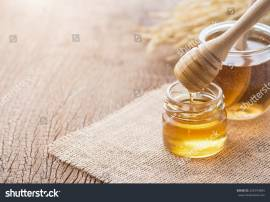 stock-photo-honey-with-wooden-honey-dipper-on-wooden-table-626754845